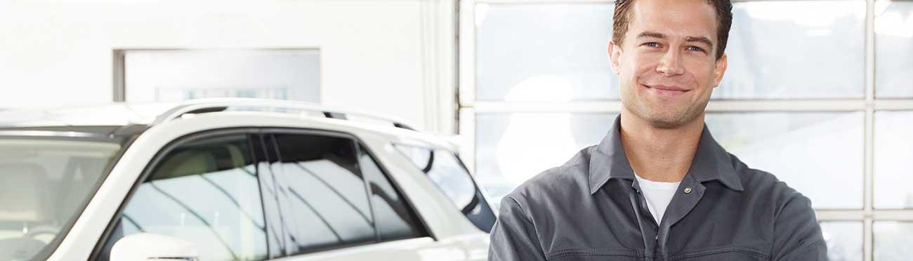 Kfz-Mechaniker steht in der Werkstatt vor einem Fahrzeug